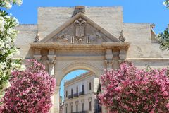 Lecce, Italy. City in Salento peninsula. Oleander flowers and Porta Napoli Triumphal Arch Stock Image