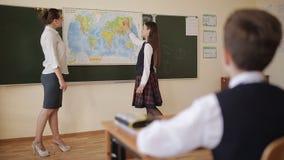 Lección de la geografía Alumno en uniforme escolar en las respuestas del mapa del mundo las cuestiones del profesor almacen de metraje de vídeo
