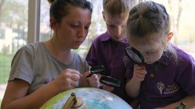 Lección de la geografía, de los alumnos y del profesor joven con la lupa estudiando el globo en guardería metrajes