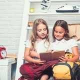 Lección de la literatura en la escuela lectura de la literatura de dos pequeños niños de las muchachas que sostienen el libro fotografía de archivo libre de regalías