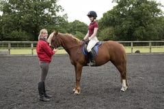 Lección de montar a caballo con el jinete y el instructor Imagen de archivo