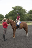 Lección de montar a caballo con el jinete y el instructor Fotografía de archivo