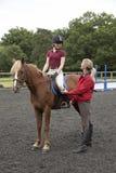 Lección de montar a caballo con el jinete y el instructor Fotos de archivo libres de regalías