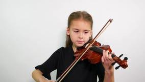 Lección de violín La cara de una muchacha que juega una canción del violín almacen de metraje de vídeo