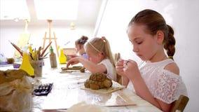 Lección del arte en taller con los niños a esculpir de la arcilla en la escuela primaria almacen de metraje de vídeo
