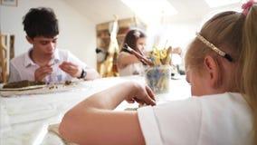 Lección del arte en taller con los niños a esculpir de la arcilla en la escuela primaria almacen de video