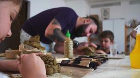 Lección del arte en taller con los niños y el hombre que les enseñan para esculpir de la arcilla almacen de video