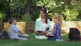 Lección en la naturaleza, los alumnos elegantes muchacho y muchacha con los libros leídos femeninos y la charla del profesor dura almacen de metraje de vídeo