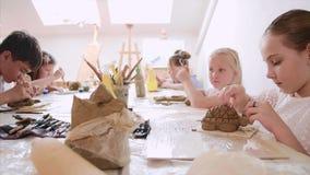 Lección en taller del arte en escuela primaria Los niños están modelando los juguetes de la arcilla almacen de video
