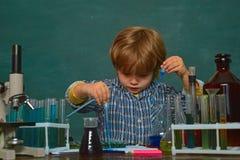 Lecci?n de la qu?mica Microscopio del laboratorio y tubos de prueba Una demostraci?n de la qu?mica De nuevo a escuela Primer grad fotografía de archivo libre de regalías