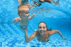 Lección de la natación del niño - bebé con la zambullida del moher subacuática en piscina Fotos de archivo