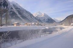 Lech del río con las ramas y las montañas congeladas Fotos de archivo