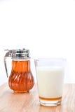 Leche caliente con la miel, el tarro de la miel y el cazo de la miel en el backgro blanco Imagenes de archivo