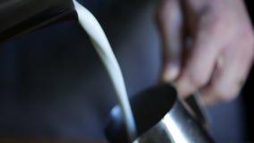 Leche caliente de Barista Pouring en la jarra de la leche almacen de metraje de vídeo