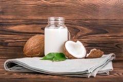 Leche de coco deliciosa, cocos orgánicos con los leves verdes frescos en un fondo de madera oscuro Fotografía de archivo libre de regalías
