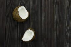 Leche de coco orgánica blanca marrón tropical fresca de la pulpa del coco en fondo negro de madera Foto de archivo libre de regalías