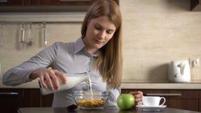Leche de colada de la empresaria atractiva joven hermosa en un cuenco de copos de maíz en la cocina almacen de metraje de vídeo