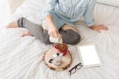 Leche de colada de la mujer joven en la taza de café mientras que se sienta en cama Foto de archivo