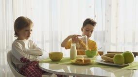 Leche de colada del muchacho en placa con las avenas, dos hermanos que desayunan almacen de video