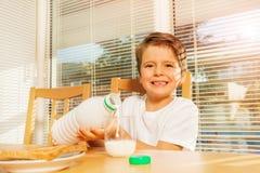 Leche de colada del muchacho feliz en el desayuno en la cocina fotos de archivo