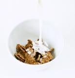 Leche de colada en un tazón de fuente con los copos de maíz Fotos de archivo libres de regalías