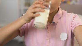 Leche de colada de la mano en el vidrio, muchacho que lo bebe con el placer, comida sana, vitamina metrajes