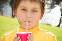 Leche de consumición de la fresa del muchacho joven al aire libre Fotos de archivo libres de regalías
