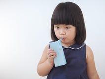 Leche de consumo de la muchacha asiática feliz del niño de la caja del cartón con la paja, paquete en blanco del jugo a disposici Fotografía de archivo libre de regalías