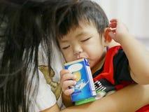 Leche de consumo del bebé asiático soñoliento fuera de un cartón con la paja fotos de archivo
