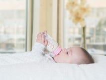 Leche de consumo del bebé de la botella en casa Imagen de archivo libre de regalías