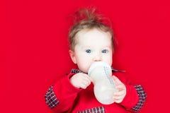 Leche de consumo del bebé lindo en una manta roja Imágenes de archivo libres de regalías