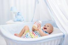 Leche de consumo del bebé Muchacho con la botella de la fórmula en cama fotos de archivo libres de regalías