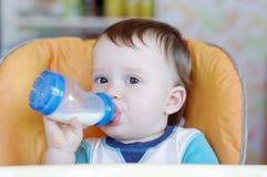 Leche de consumo del bebé precioso de una pequeña botella Imágenes de archivo libres de regalías