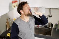 Leche de consumo del hombre por la mañana en cocina de la botella fotografía de archivo libre de regalías