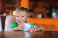 Leche de consumo del niño pequeño feliz en café Foto de archivo libre de regalías