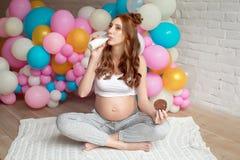 Leche de consumo de la mujer embarazada de los jóvenes que se sienta en piso en el cuarto Imagen de archivo libre de regalías