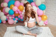 Leche de consumo de la mujer embarazada de los jóvenes que se sienta en piso en el cuarto Fotografía de archivo
