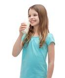 Leche de consumo sonriente de la niña fuera del vidrio Imagenes de archivo
