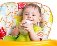 Leche de consumo sonriente del bebé de la botella Fotos de archivo libres de regalías