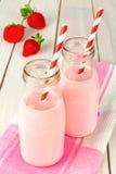 Leche de la fresa en botellas en la tabla Foto de archivo libre de regalías