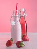Leche de la fresa y jugo de la fresa en botellas Foto de archivo libre de regalías