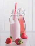 Leche de la fresa y jugo de la fresa en botellas Fotos de archivo libres de regalías