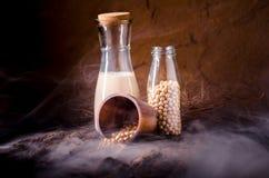 Leche de soja con algunas semillas en fondo de madera Fotos de archivo
