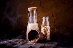 Leche de soja con algunas semillas en fondo de madera Fotos de archivo libres de regalías
