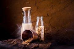 Leche de soja con algunas semillas en fondo de madera Imagen de archivo libre de regalías