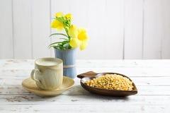 Leche de soja y haba de la soja con la flor en la tabla de madera Foto de archivo libre de regalías