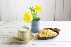 Leche de soja y haba de la soja con la flor en la tabla de madera Imagen de archivo
