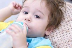 leche del bebé de 7 meses que come la botella Fotos de archivo libres de regalías