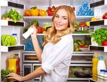 Leche elegida mujer en refrigerador abierto Foto de archivo