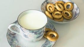 Leche en una taza en la tabla con el pan, secándose imágenes de archivo libres de regalías